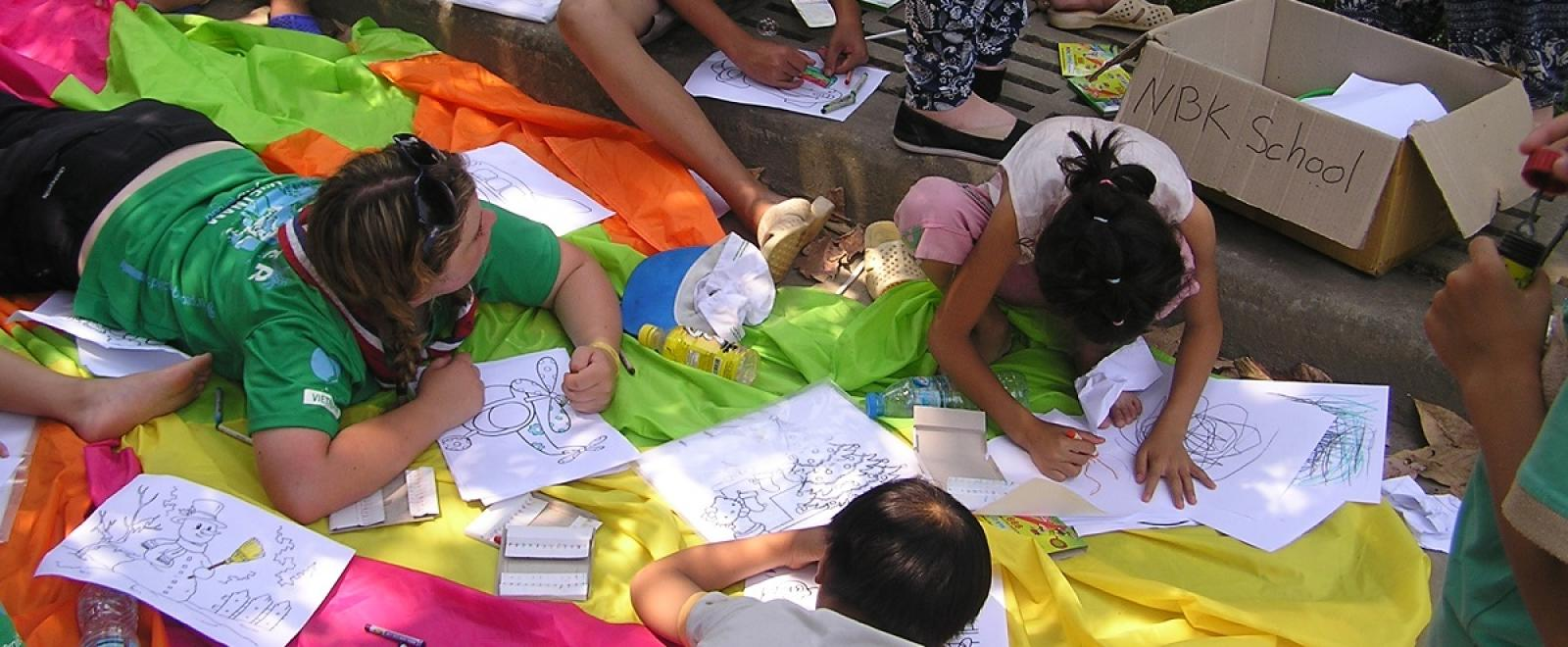 Projects Abroad volunteers work on homework and drawing activities with children in Vietnam on the Childcare Project